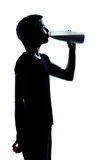 One young teenager girl drinking milk silhouette Stock Photos