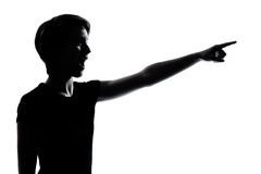 One young teenager pointing surprised silhouette. One caucasian young teenager silhouette boy or girl pointing surprised  portrait in studio cut out isolated on Stock Image