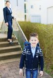 One young white boy goes to school. mom on background. Stock Photos
