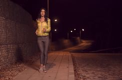 One young woman, alone one person, jogging sidewalk, outdoors ni. One young woman, alone one person, jogging ewalk, outdoors night nighttime, street lights Stock Images