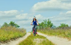 One young woman - an athlete in a helmet riding a mountain bike outside the city. On the road on a summer day Stock Photo