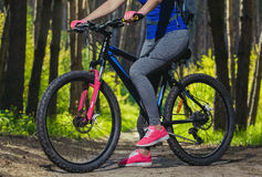 One young woman - an athlete in the pink shoes walks with the mountain bike in a pine forest Royalty Free Stock Photography