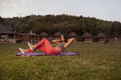 One young woman, fitness, abs, push up exercise mat, outdoors, e. Tho ethno houses village cottage outdoors, grass field, sport clothes Royalty Free Stock Images