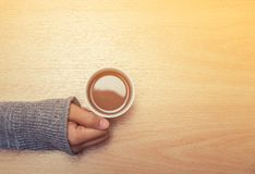 One of young woman hands holding a cup of hot drink on the woode. N table Royalty Free Stock Photos
