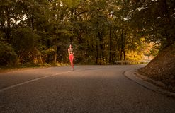 One young woman, outdoors jogging running on asphalt road, fores Stock Image