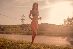 One young woman, outdoors jogging, sport clothes, Sun sky sunny, Royalty Free Stock Photos
