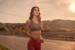 One young woman, outdoors jogging walking, sport clothes, Sun sk Stock Images
