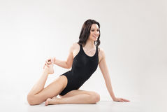 One young woman, sitting, stretching leg Royalty Free Stock Image