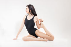 One young woman, stretching leg, sitting swimsuit Stock Photo