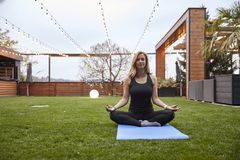One young woman,20-29 years old, doing yoga while sitting in a sukhasana pose in a beautiful backyard, stock image