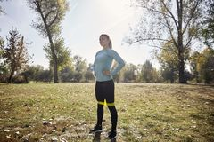 One young woman, 20-29 years old, full length shot, standing proud in public park. stock image