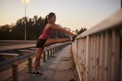 One young woman, 20-29 years, stretching legs alone on a bridge. night time, sunset.  royalty free stock image