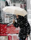One young women walking under umbrella in heavy snowfall in city street stock photo