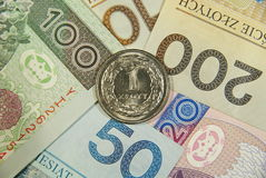 One zloty on all of polish cash. One zloty coin on background make by all of polish paper currency Royalty Free Stock Photos