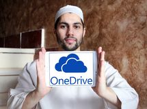 OneDrive logo. Logo of microsoft onedrive on samsung tablet holded by arab muslim man. it is a file-hosting service operated by Microsoft as part of its suite of Royalty Free Stock Photo