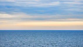 Oneindig oceaanlandschap in een bewolkte zonsondergangtijd royalty-vrije stock afbeelding
