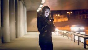 Onelyvrouw het typen tekstbericht op de donkere straat Stock Afbeeldingen