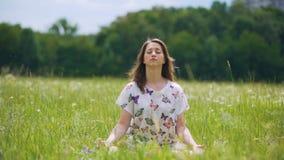 Oneness met aard, jonge vrouwelijke donkerbruine gesloten ogen en mediteert in openlucht stock footage