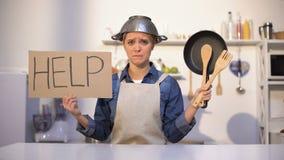 Onervaren huisvrouw die om hulp in koken vragen, die pot op hoofd, grap dragen stock footage