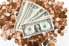 Ones and Pennies. Several one dollar bills on top of a pile of pennies. American currency. White background Stock Images