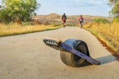 Onewheel elektrische skateboard en fietsers Royalty-vrije Stock Foto's