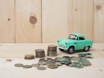 oney硬币堆积生长与在木背景的绿色汽车 Busi 免版税库存图片