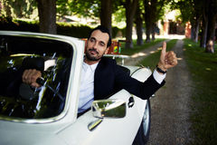 Сonfident handsome man sits in his new convertible car doing super gesture with the finger Stock Photos