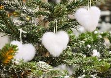 Ongebruikelijke creatieve romantische Kerstmis of Nieuwjaardecoratie - wit pluizig Kerstmisspeelgoed van de hartvorm op sparren i Stock Afbeelding