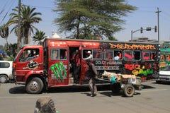 Ongebruikelijke geschilderde rode stadsbus in Nairobi stock foto