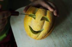 Ongebruikelijke Halloween-meloen, scherp proces, mes en mannelijke handen Stock Afbeeldingen