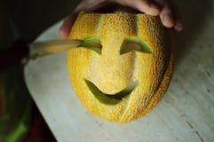 Ongebruikelijke Halloween-meloen, scherp proces, mes en mannelijke handen Royalty-vrije Stock Fotografie