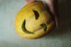 Ongebruikelijke Halloween-meloen, scherp proces, mes en mannelijke handen Stock Afbeelding