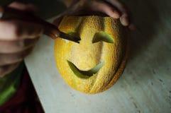 Ongebruikelijke Halloween-meloen, scherp proces, mes en mannelijke handen Stock Fotografie