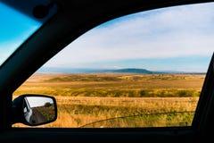 Ongebruikelijke hoek van het autoraampanorama van een mooi landschap met bergketens in Kazachstan Stock Foto