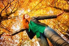 Ongebruikelijke hoek van jonge vrouw in de herfstpark stock fotografie