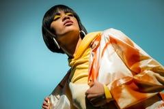 Ongebruikelijke kortharige vrouw die heldere oranje poncho dragen royalty-vrije stock afbeelding