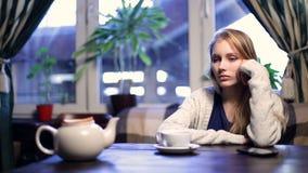 Ongeduldig meisje die op haar vriend in koffie wachten stock footage