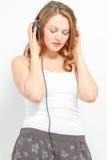 Ongehaaste het meisje luistert aan audio Stock Foto