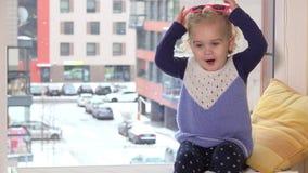 Ongehoorzaam meisje die met zonnebril op radiator dichtbij venster zitten Sneeuw het Vallen stock footage