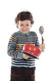 Ongehoorzame jongen die lawaai met een steelpan maakt stock foto's