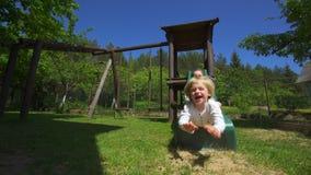 Ongehoorzame van het jonge geitjesjongen en meisje dia neer en lach op privé speelplaats Handbediend stock footage