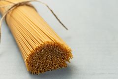 Ongekookte deegwarenspaghetti op een blauwe achtergrond stock fotografie