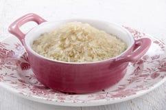 Ongekookte langkorrelige rijsten in een kom royalty-vrije stock fotografie