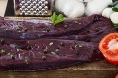 Ongekookte lever met kruidenknoflook en tomaten Stock Afbeeldingen