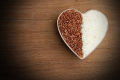 Ongekookte organische rijst en rode rijst in een plastic kom Stock Foto