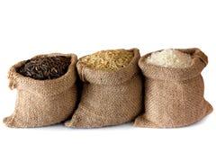 Ongekookte rijst in kleine jutezakken Stock Foto's
