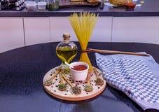 Ongekookte spaghetti en kruiden op houten plaat Stock Foto's