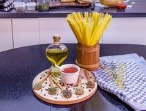 Ongekookte spaghetti in houten pot en kruiden op houten plaat Stock Fotografie