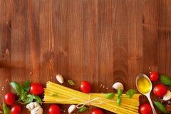 Ongekookte spaghetti, kersentomaat, basilicum, knoflook en olijfolie, ingrediënten voor het koken van deegwaren, voedselachtergro Stock Foto