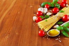 Ongekookte spaghetti, kersentomaat, basilicum, knoflook en olijfolie, ingrediënten voor het koken van deegwaren, voedselachtergro Stock Fotografie